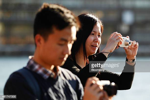 Tourists take photographs with cameras near the Sydney Opera House in Sydney Australia on Tuesday July 21 2015 Tired hotels outdated attractions like...