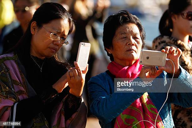 Tourists take photographs with their Apple Inc iPhones near the Sydney Opera House in Sydney Australia on Tuesday July 21 2015 Tired hotels outdated...