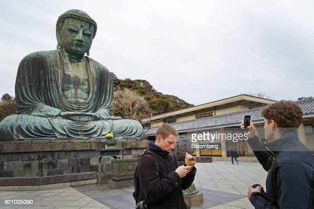 Tourists take photographs with their smartphones in front of the Great Buddha at the Kotokuin temple in Kamakura Kanagawa Japan on Monday Feb 19 2018...