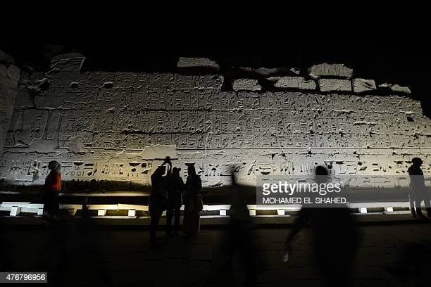 Tourists take photos and walk past hieroglyphics at Karnak temple in Luxor a town 700 kilometres south of the Egyptian capital Cairo in the evening...
