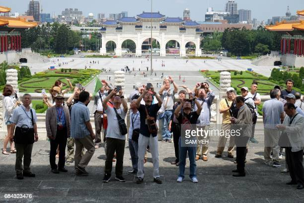 Tourists take photos at the Chiang Kaiskek Memorial Hall in Taipei on May 18 2017 Visitor numbers to Taiwan fell in the first quarter dragged down by...