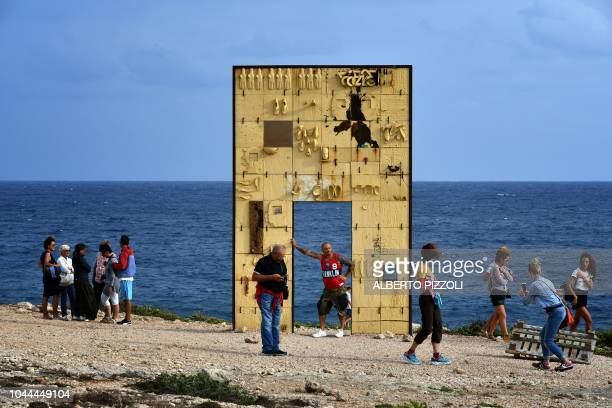 Tourists take photos at the Porta di Lampedusa known as The door of Europe a monument to the migrants who have died in the Mediterranean located at...