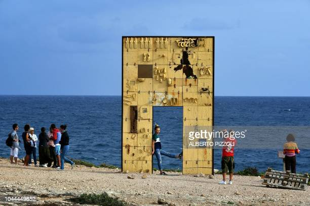 TOPSHOT Tourists take photos at the Porta di Lampedusa known as The door of Europe a monument to the migrants who have died in the Mediterranean...