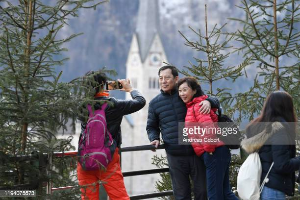 Tourists take photos in the town center on January 16 2019 in Hallstatt Austria Hallstatt known for its picturesque beauty and its location at the...