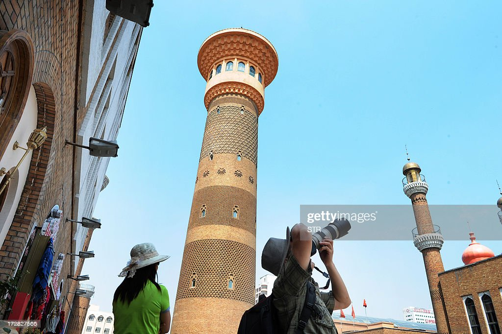 Tourists take photos of a mosque near the city bazaar in Urumqi, farwest China's Xinjiang region on July 5, 2013. Chinese authorities imposed tight control in the capital of Xinjiang on July 5, the fourth anniversary of ethnic rioting which killed around 200 people, said state media and exile groups. CHINA