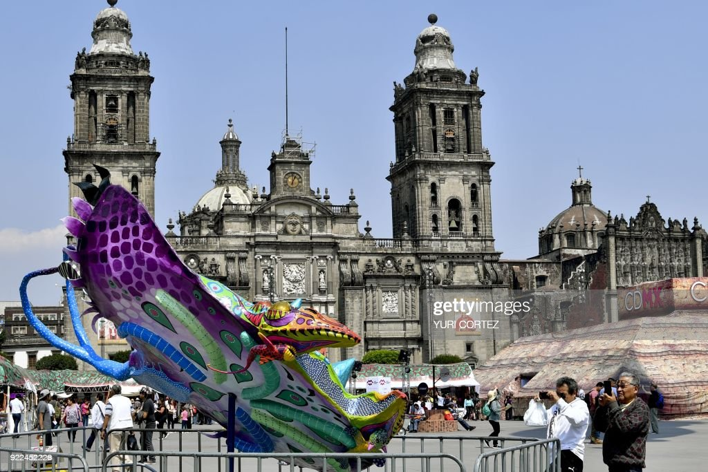Tourists take photos of an alebrije - traditional Mexican folk art sculptures representing fantastical creatures - on exhibit at the El Zocalo square during the 'In the heart of Mexico festival' in Mexico City on February 21, 2018. Representatives of all Mexican states present samples of their food, clothing and traditions during the festival. /