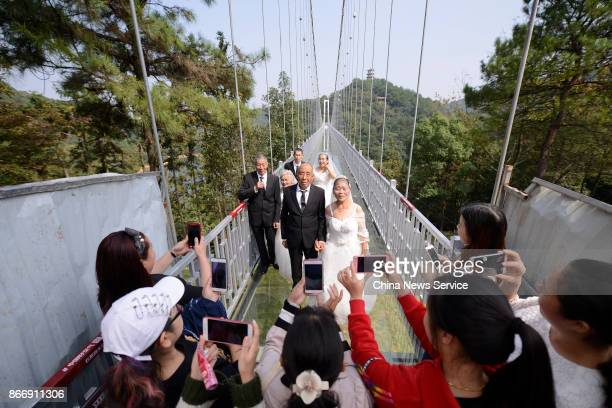 Tourists take photos of four couples in wedding dress attire who pose for a photo in celebration of their golden wedding anniversary on a transparent...
