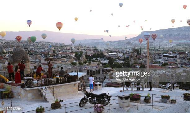 Tourists take photos of hot air balloons glide over the historical Cappadocia region from their hotel's terrace in Central Anatolia's Nevsehir...