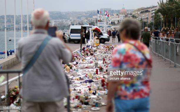 Tourists take photos of plush toys and candles lying on the 'Promenade des Anglais' in Nice France 14 September 2016 A 31yearold Tunisian man had...