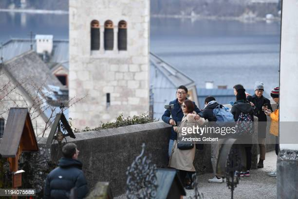 Tourists take photos on a cemetery in the town center on January 16, 2019 in Hallstatt, Austria. Hallstatt, known for its picturesque beauty and its...