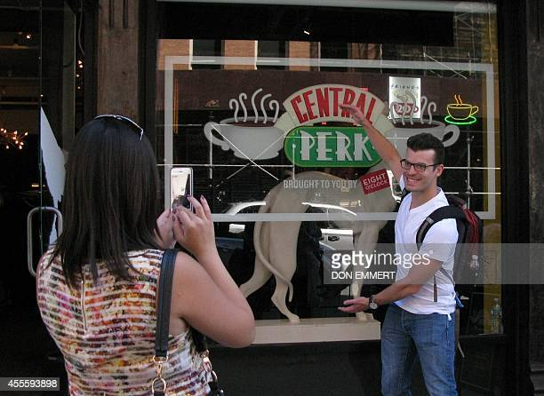 Tourists take photos outside a temporary pop up reproduction of the Central Perk coffee shop a center piece set of the television situation comedy...