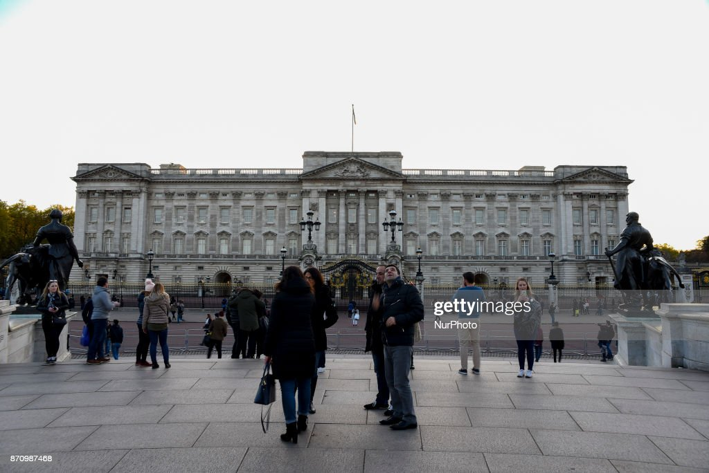Tourists take photos to Buckingham Palace as the sun sets, London on November 6, 2017. About £10m of the Queen's private money was invested offshore, leaked documents show. The Duchy of Lancaster, which provides the Queen with an income, held funds in the Cayman Islands and Bermuda.