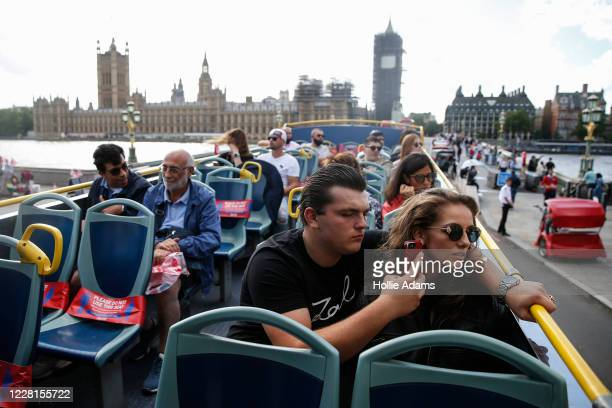 Tourists take pictures as they cross Westminster Bridge on a sightseeing bus on August 22, 2020 in London, England. Whilst the UK is open for...