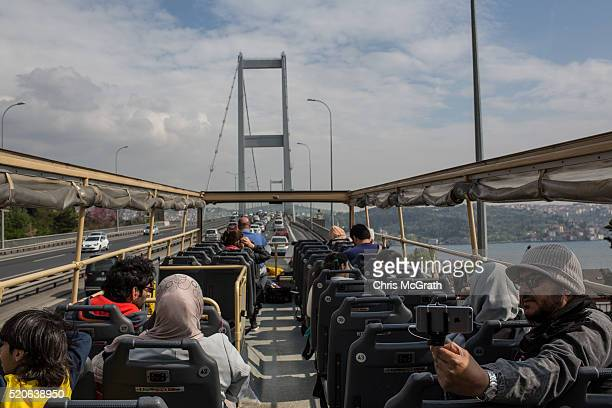 Tourists take pictures as they ride a tourist bus over the Bosphorus bridge on April 12 2016 in Istanbul Turkey Turkey's recent string of terrorist...