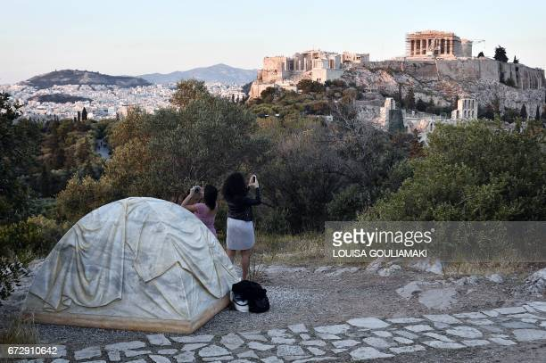 Tourists take pictures as they stand next to an installation by Canadian artist Rebecca Belmore a tent in marble symbolising the refugee crisis in...