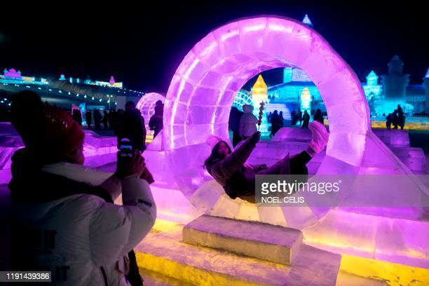 Tourists take pictures at an ice sculpture ahead of the opening of the Harbin International Ice and Snow Festival in Harbin in China's northeast...