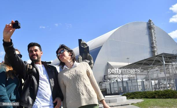 Tourists take pictures at Chernobyl's New 108 metres Safe Confinement covering the 4th block of Chernobyl Nuclear power plant during their tour to...