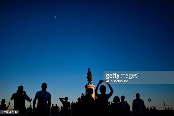 Tourists take pictures at Comercio square in Lisbon on August 2 2017 / AFP PHOTO / PATRICIA DE MELO MOREIRA