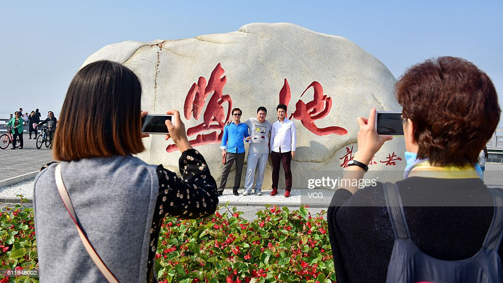 Tourists take pictures at the colorful salt lake scenic spot on October 2, 2016 in Yuncheng, Shanxi Province of China. The salt lake displaying red and green colors in Yuncheng attract tourists during the National Day holiday. Formed about 500 million years ago, the salt lake owns different colors as a result of the algae in the water.