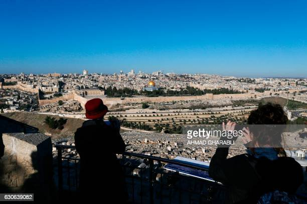 Tourists take pictures during a visit to the Mount of Olives in east Jerusalem overlooking the Old City and the AlAqsa mosque compound on December 29...
