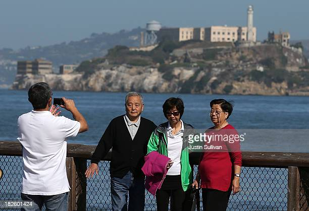 Tourists take pictures in front of Alcatraz Island on October 1 2013 in San Francisco California Visitors were given refunds for their purchased...