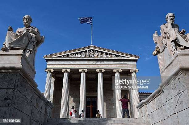 Tourists take pictures in front of the Athens Academy adorned with sculputures depicting ancient greek philosophers Plato and Sokrates on June 10...