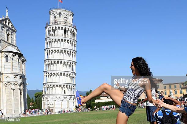 Tourists take pictures in front of the Leaning Tower of Pisa Torre pendente di Pisa on August 10 2013 in Pisa Italy