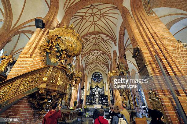 Tourists take pictures inside the Cathedral known as Storkyrkan situated near the Royal Castle in Stockholm on May 25 less than a month before Crown...