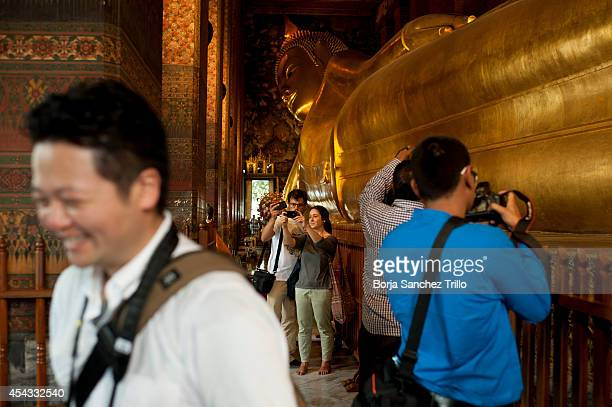 Tourists take pictures inside Wat Pho temple on August 29, 2014 in Bangkok, Thailand. Thai government has approved a regulation that allows tourists...
