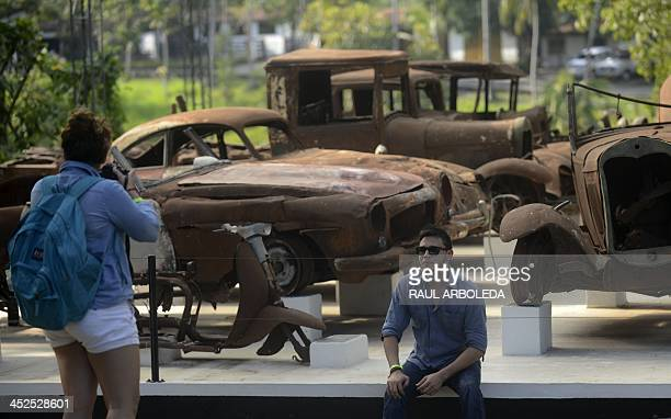 Tourists take pictures next to cars which belonged to Colombian drug lord Pablo Escobar at the Napoles Ranch theme park in the Puerto Triunfo...