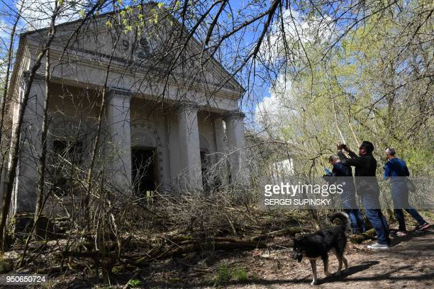 Tourists take pictures of a building in the ghost village of Kopachi near Chernobyl Nuclear power plant on April 23 2018 during their tour to the...