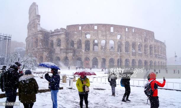 Tourists take pictures of the ancient Colosseum during a snowfall in Rome on February 26 2018 / AFP PHOTO / Vincenzo PINTO