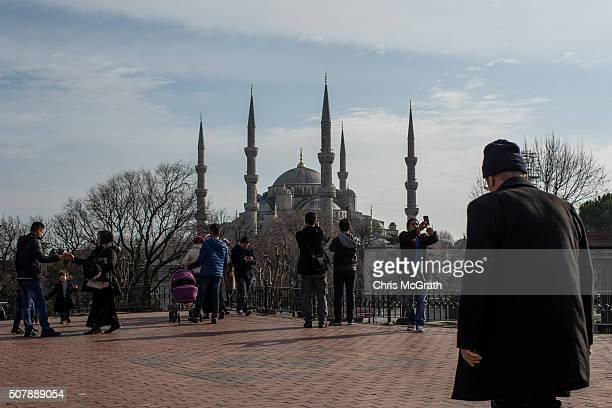 Tourists take pictures of the Blue Mosque in the famous Sultanahmet District on February 1 2016 in Istanbul Turkey People continue to visit the...
