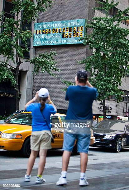 Tourists take pictures of the National Debt Clock billboard on a building in midtown Manhattan on August 2 2011 in the New York City The national...