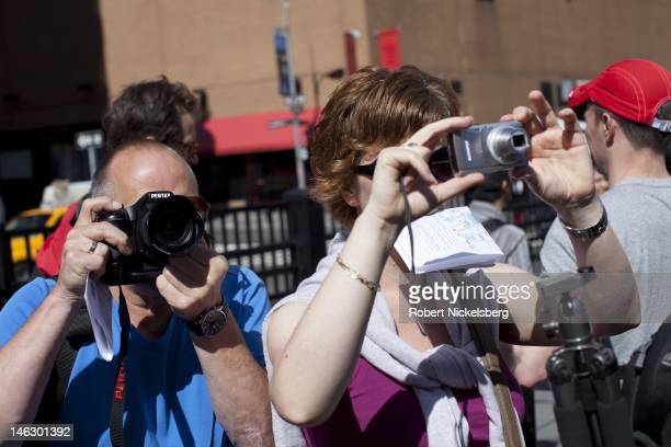 Tourists take pictures of the new World Trade Center buildings under construction June 6 2012 while waiting to enter the 911 Memorial area at Ground...