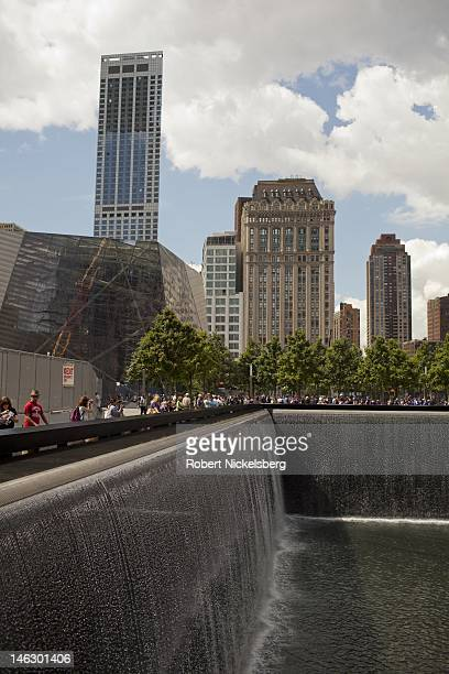 Tourists take pictures of the North Pool at the 911 Memorial June 6 2012 in New York City The lower Manhattan neighborhoods and important historical...