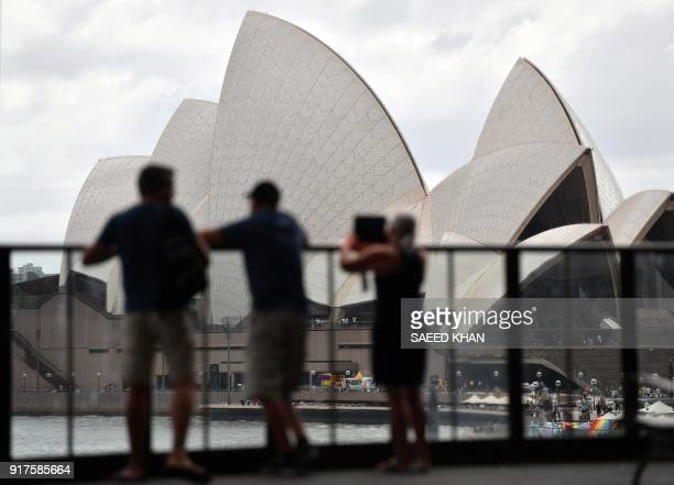 Tourists take pictures of the Opera House from Circular Quay station in Sydney on February 13 2018 Australia's central bank on February 6 kept...