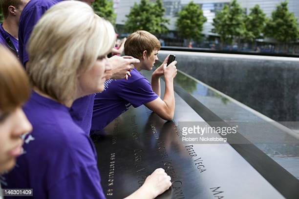 Tourists take pictures of the South Pool at the 911 Memorial June 6 2012 in New York City The lower Manhattan neighborhoods and important historical...