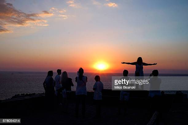 Tourists take pictures of the sunset ower the Aegaen sea in town on July 18 2016 in Molivos Lesvos island Greece The increase in refugees arriving on...