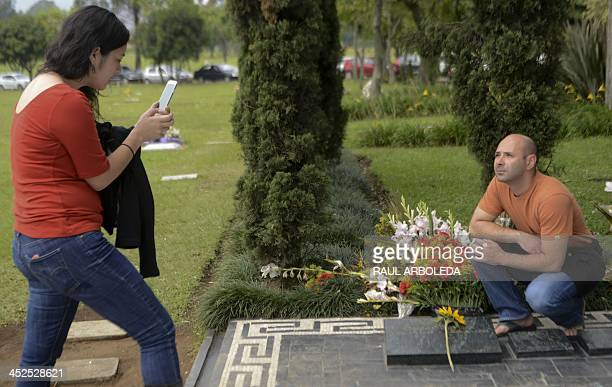 Tourists take pictures of the tomb of Colombian drug lord Pablo Escobar on November 25 2013 at the Montesacro cemetery in Medellin Antioquia...