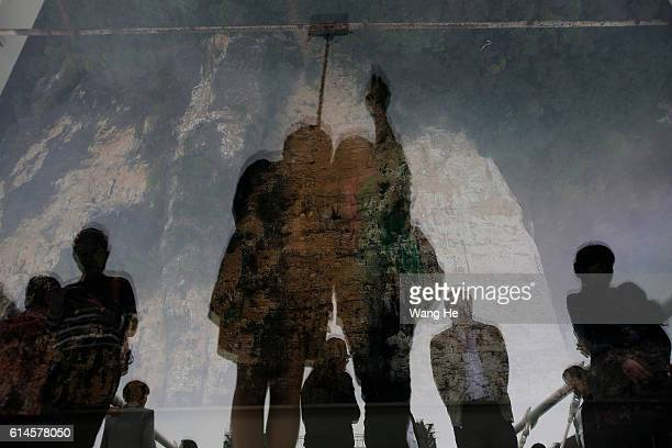 Tourists take pictures of their shadows on the glassfloor suspension bridge in Zhangjiajie in south China's Hunan province on October 14 2016 in...