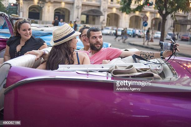 Tourists take pictures of themselves before a site seeing trip in a vintage car in Old Havana on September 25 2015 A great number of tourist visits...