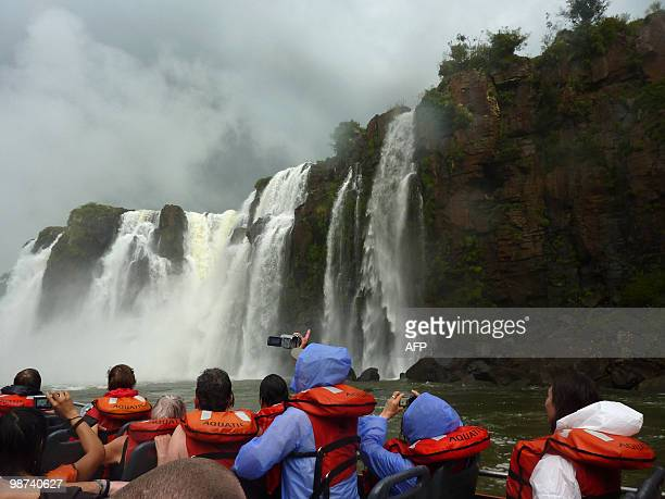Tourists take pictures on an adventure boat of the Iguacu Falls on the Argentinian side of the Iguazu River on April 28 2010 The waterfall system...
