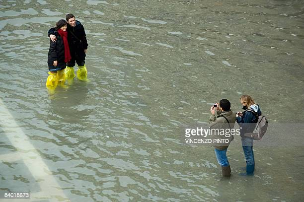 Tourists take pictures on Piazza San Marco during floods on December 13 2008 in Venice The acqua alta stood at 109 centimeters in the morning while...