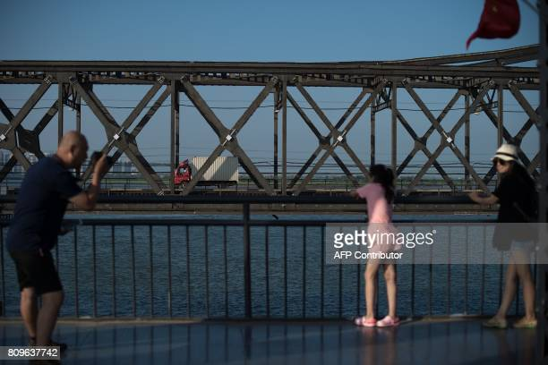 Tourists take pictures on the Broken bridge as a truck drives from North Korea's Sinuiju across the Yalu river to the Chinese border city of Dandong...