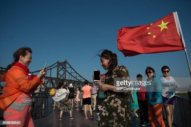 Tourists take pictures on the the Broken Bridge next to the Friendship bridge on the Yalu River connecting the North Korean town of Sinuiju and the...