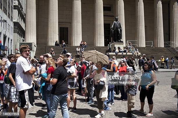 Tourists take pictures on Wall Street in front of Federal Hall and a statue of George Washington June 7 2012 across from the New York Stock Exchange...