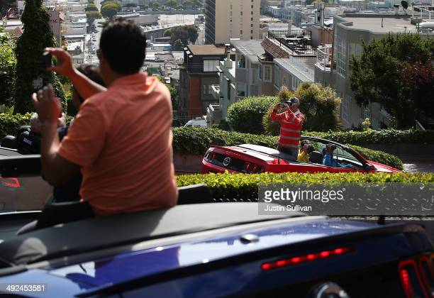 Tourists take pictures while driving down Lombard Street on May 20 2014 in San Francisco California The San Francisco Municipal Transportation Agency...