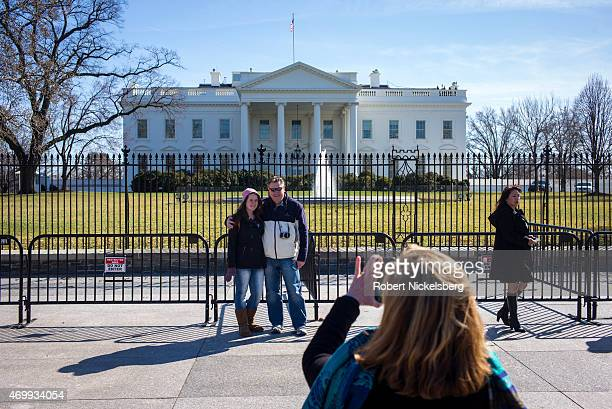 Tourists take pictures while standing in front of the White House March 18, 2015 in Washington, DC. The U.S. Secret Service, in charge of White House...