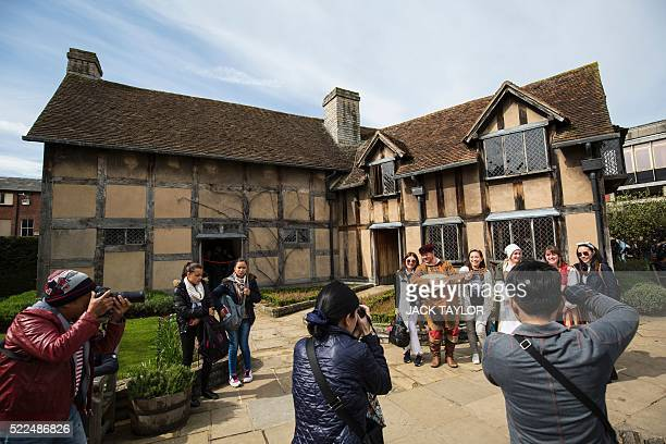 Tourists take pictures with actors outside the house where British poet and playwright William Shakespeare was thought to be born in...